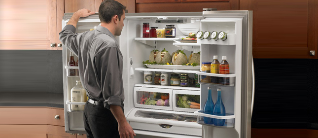 man looking in refrigerator whirlpool repair